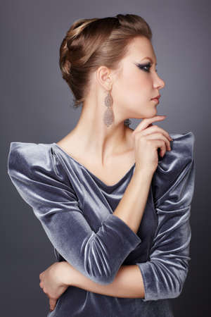 sideview portrait of beautiful young brunette woman in stylish dress touching chin photo