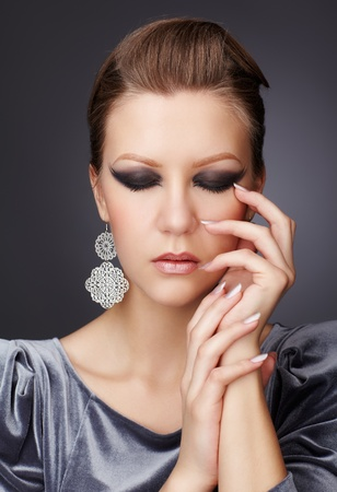 portrait of beautiful young brunette woman in fancy dress with manicured fingers closing eyes photo