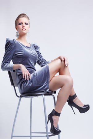 full-length portrait of beautiful young brunette woman in stylish dress sitting on bar chair Stock Photo