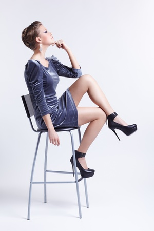 portrait of beautiful young brunette woman in stylish dress sitting on bar stool and touching her chin photo