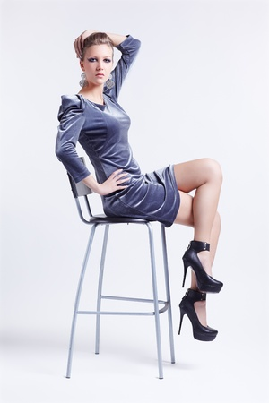 portrait of beautiful young brunette woman in stylish dress and court shoes sitting on bar stool photo