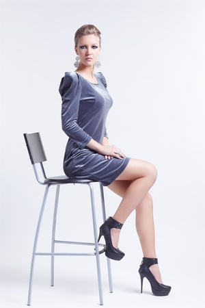 portrait of beautiful young brunette woman in stylish dress and court shoes sitting on bar chair