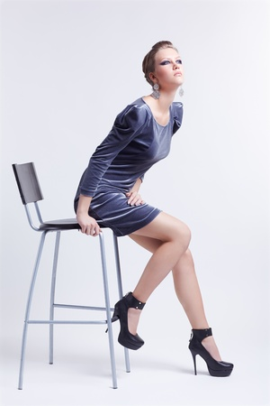 portrait of beautiful young brunette woman in fancy dress and court shoes sitting on bar chair photo