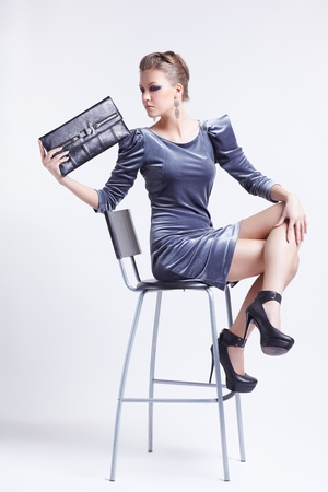 full-length portrait of beautiful young brunette business woman in stylish dress sitting on bar chair with clutch in hand Stock Photo - 13208604