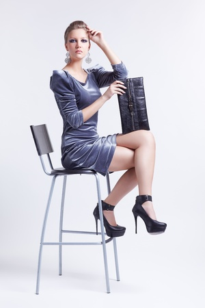 full-length portrait of beautiful young brunette business woman in stylish dress sitting on bar chair with clutch Stock Photo - 13208606
