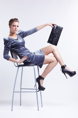 full-length portrait of beautiful young brunette business woman in stylish dress sitting on bar stool with clutch in hand photo
