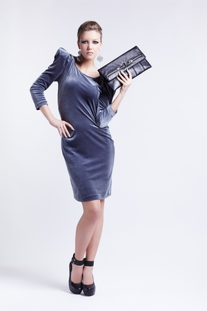 full-length portrait of beautiful young brunette woman in stylish dress holding clutch in hand on gray photo