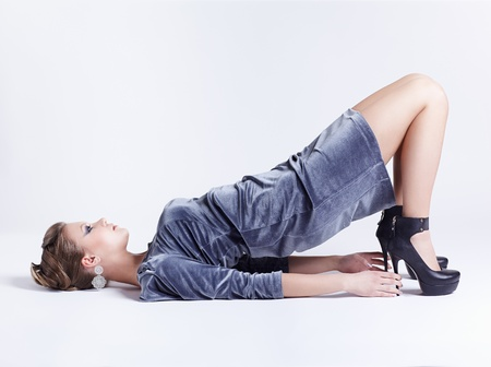 full-length portrait of beautiful young brunette woman in stylish dress lying on the floor on gray photo