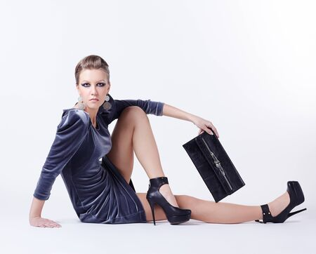 full-length portrait of beautiful young brunette woman in stylish dress sitting on the floor with clutch in hand photo