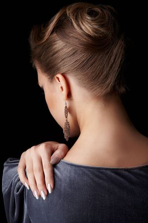 back portrait of beautiful young brunette woman touching her shoulder with manicured hand on black photo