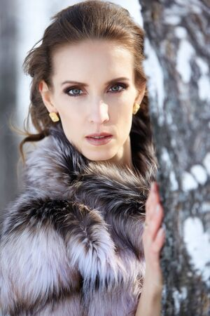 outdoor portrait of beautiful brunette woman in fur coat posing near birch in snowy winter forest photo