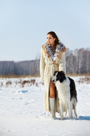 european white birch: outdoor portrait of beautiful brunette woman with borzoi in snowy filed with winter forest on background Stock Photo