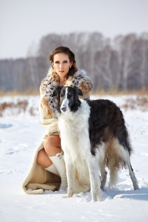 portrait of beautiful brunette woman with russian wolfhound in fur coat in snowy filed with winter forest on background photo