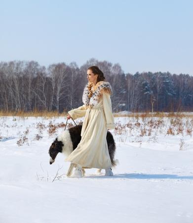 mujer con perro: al aire libre retrato de mujer hermosa morena con perro lobo ruso en la nevada presentada en bosque de invierno en el fondo Foto de archivo