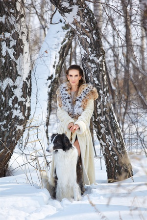 outdoor portrait of beautiful brunette woman with russian wolfhound in snowdrift in winter forest photo