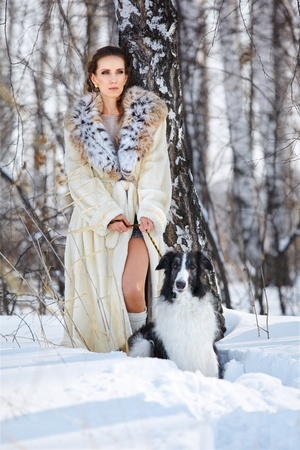 outdoor portrait of beautiful brunette woman with russian wolfhound in snowdrift in winter birch forest photo