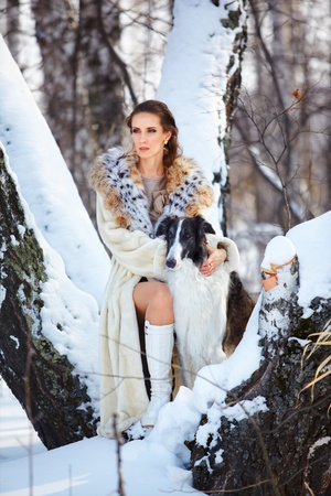 snowdrift: outdoor portrait of beautiful brunette woman with russian wolfhound in snowy winter forest