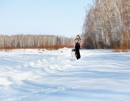 mujer con perro: al aire libre retrato de la bella mujer morena con perro Borzoi en el bosque de invierno cubierto de nieve