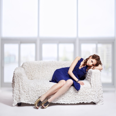 full-length portrait of beautiful tired young brunette woman in blue dress sitting on sofa with large windows on background photo