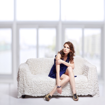 full-length portrait of beautiful young brunette woman in blue dress sitting on sofa with large windows on background Stock Photo