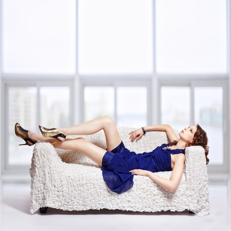 full-length portrait of beautiful young brunette woman in blue dress lying on sofa with large windows on background photo