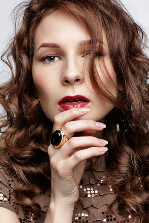 portrait of beautiful young brunette woman with large styilsh ring on her hand photo