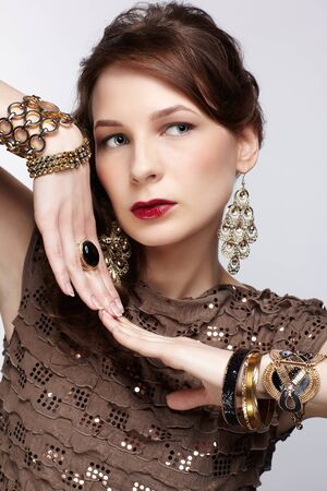 portrait of beautiful young brunette woman in ring, ear-rings and several braceletes on gray Stock Photo - 13287058
