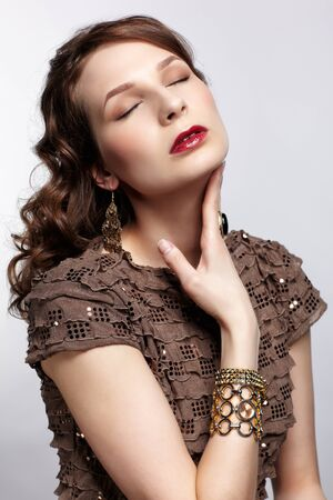 portrait of beautiful young brunette woman in vaus jewelry touching her neck and closing eyes Stock Photo - 13287054