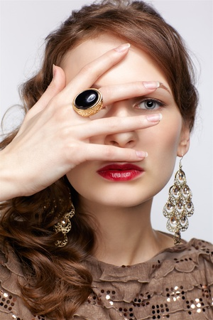 portrait of beautiful young brunette woman in ring and ear-rings with manicured fingers Stock Photo - 13287041