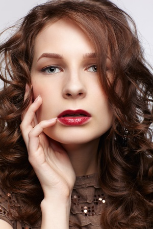 portrait of beautiful young brunette woman touching her face with manicured fingers on gray photo
