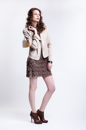 portrait of beautiful young brunette woman in dress, jacket and boots with clutch in hand photo