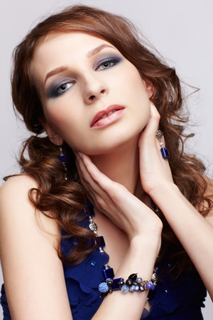 portrait of beautiful young brunette woman in blue dress, beads, bracelet and ear-rings on gray photo