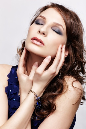 portrait of beautiful young brunette woman in blue dress and bracelet touching her face and closing eyes photo