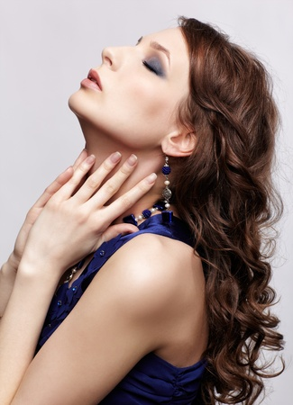 sideview portrait of beautiful young brunette woman in blue dress and jewellery touching her neck Stock Photo - 13287050