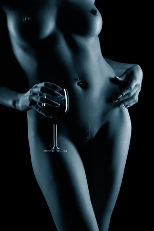body part portrait of young naked woman with beautiful breasts with glass of red wine in hand