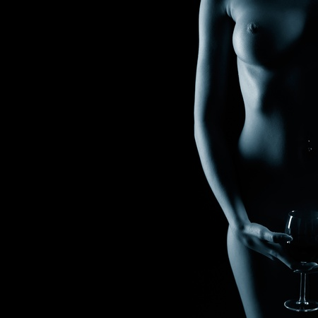 naked legs: body part portrait of young naked woman with beautiful breasts with glass of red wine in hand