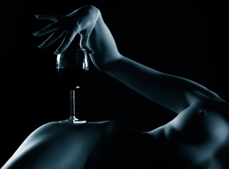 mujer desnuda senos: retrato de cuerpo de parte de la joven desnuda con pechos hermosos con vaso de vino tinto en la cadera