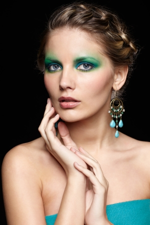 portrait of beautiful young woman with green and blue eye shade make up touching her face photo