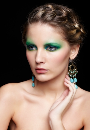 portrait of beautiful young woman with green and blue eye shade make up touching her neck photo