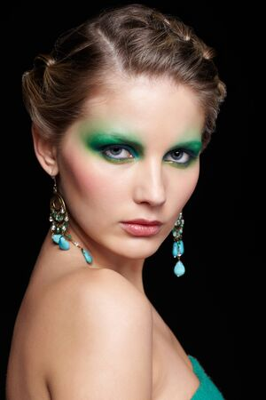 portrait of beautiful young woman with green and blue eye shade make up posing on black photo