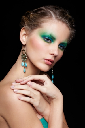 portrait of beautiful young woman with green and blue eye shade make up touching shoulder Stock Photo - 13675572