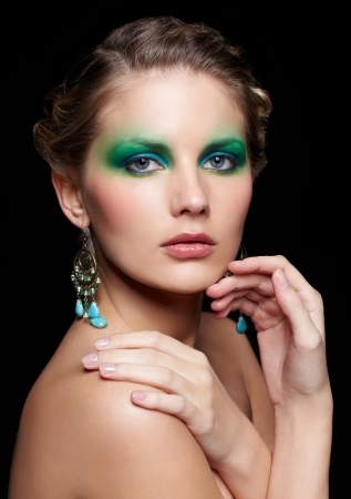 portrait of beautiful young woman with green and blue eye shade make up touching shoulder and chin photo
