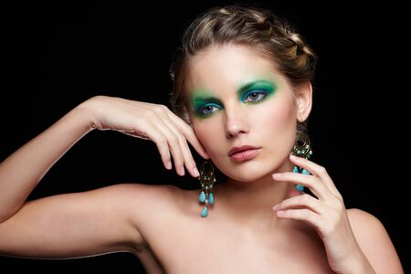 portrait of beautiful young woman with green and blue eye shade makeup touching face and neck photo