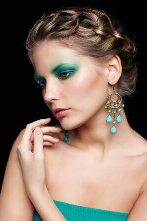 portrait of beautiful young woman with green and blue eye shade makeup touching her shoulder photo
