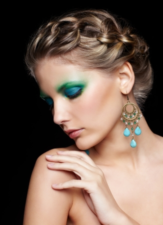 portrait of beautiful young woman with green and blue eye shade make-up touching shoulder with eyes closed