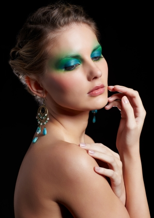 portrait of beautiful young woman with green and blue eye shade make-up touching her cheek Stock Photo - 13675574