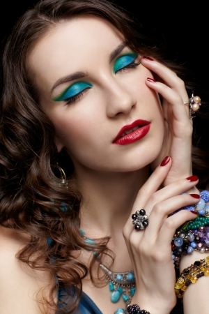 portrait of young beautiful brunette woman in ring, bracelet and beads closing eyes photo