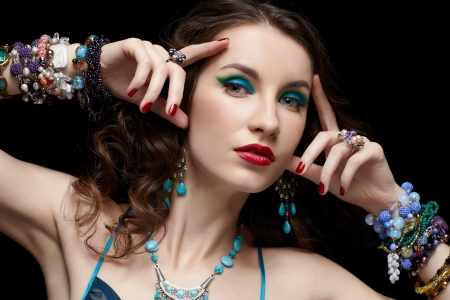 portrait of young beautiful brunette woman in jewelery on black