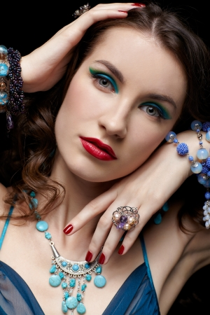 portrait of young beautiful brunette woman in jewelry on black touching her face photo