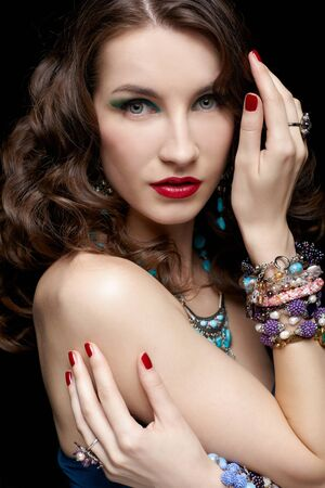 portrait of young beautiful brunette woman in jewellery on black touching her hair and shoulder photo